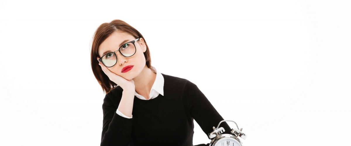 Image of tired young business lady wearing glasses sitting near alarm clock at the table isolated over white background. Looking aside.